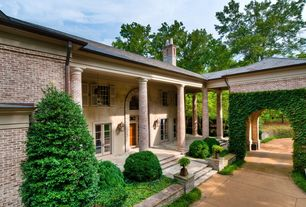 Traditional Exterior of Home with Open archway, Exterior window shutters, Arched doorway, Covered patio, Brick column