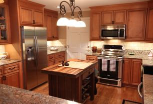 Country Kitchen with Simple granite counters, six panel door, Kitchen island, can lights, full backsplash, Pendant light