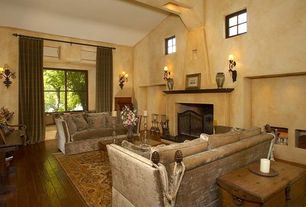 Mediterranean Living Room with High ceiling, Fireplace, Hardwood floors, Wall sconce, stone fireplace, picture window