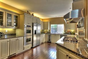Traditional Kitchen with Built In Refrigerator, dishwasher, Raised panel, Glass panel, Bamboo floors, Simple Granite, Galley