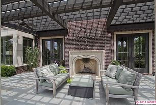 Traditional Patio with French doors, Grey wood outdoor sofas, Tudor arch stone fireplace, exterior tile floors, Trellis