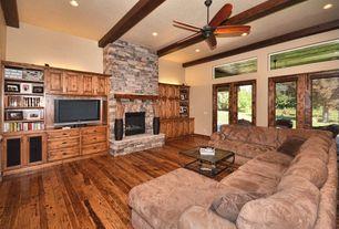 Craftsman Living Room with Hardwood floors, Built-in bookshelf, Exposed beam, interior brick, French doors, Ceiling fan