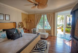 Tropical Guest Bedroom with Crown molding, Ceiling fan, Hardwood floors, Pendant light