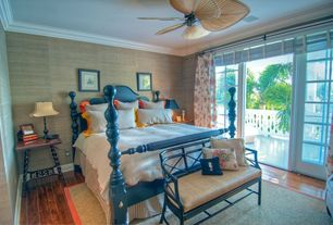 Tropical Guest Bedroom with Ceiling fan, Hardwood floors, Crown molding, French doors, interior wallpaper, Standard height
