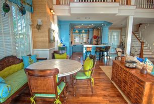 Tropical Dining Room with Columns, Wall sconce, Chair rail, Hardwood floors