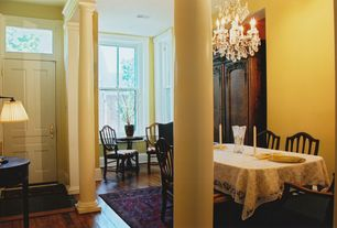 Traditional Dining Room with High ceiling, Hardwood floors, Columns, Chandelier, Built-in bookshelf