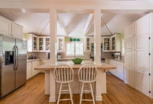 Cottage Kitchen with Interior white columns, Limestone counters, Horizontal toast solid bamboo flooring, Wood counters, Flush