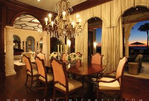 Traditional Dining Room with High ceiling, can lights, Chandelier, Hardwood floors, Crown molding, Arched window, Columns