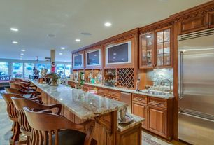 Traditional Bar with Pental kashmir gold/madura gold polished granite, Concrete floors, Built-in bookshelf, Crown molding