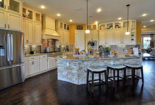 Traditional Kitchen with L-shaped, Hardwood floors, Pendant light, Custom hood, Raised panel, Glass panel, Stone Tile