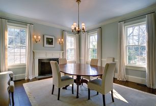 Traditional Dining Room with stone fireplace, Wall sconce, Crown molding, Hardwood floors, Chandelier