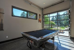 Modern Game Room with Built-in bookshelf, High ceiling, Casement, Concrete floors, specialty door, can lights