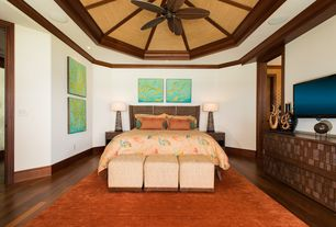 Tropical Master Bedroom with Ceiling fan, Crown molding, Built-in bookshelf, Hardwood floors