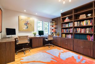 Modern Home Office with Chandelier, can lights, Built-in bookshelf, picture window, Standard height, Hardwood floors
