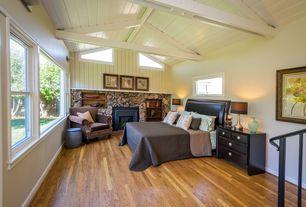 Rustic Master Bedroom with Wall sconce, Exposed beam, metal fireplace, Hardwood floors, Built-in bookshelf
