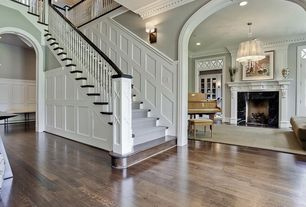 Traditional Staircase with Wall sconce, Hardwood floors, High ceiling, Wainscotting, Crown molding