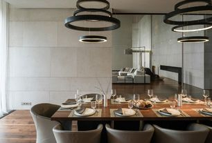 Modern Dining Room with Textured concrete walls, Modern led tiered ring chandelier pendant, mirrored walls, Standard height