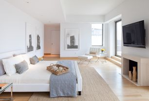 Contemporary Master Bedroom with Hardwood floors, stone fireplace, Barcelona white leather accent chair, flat door, Paint