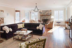Modern Living Room with Chandelier, stone fireplace, Crown molding, Hardwood floors, Glass panel door
