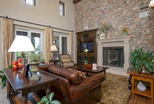 Traditional Living Room with stone fireplace, Hardwood floors, High ceiling, Wall sconce, Built-in bookshelf