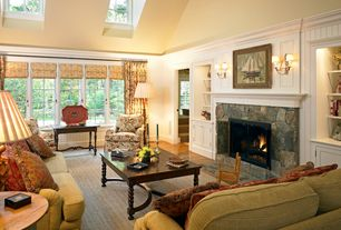 Traditional Living Room with Built-in bookshelf, Fireplace, Casement, stone fireplace, Wainscotting, Wall sconce