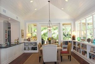 Cottage Dining Room with High ceiling, Built-in bookshelf, Paintable white beadboard, Seagrass chair - honey, Pendant light