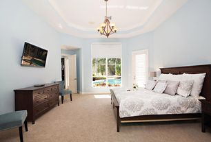 Traditional Master Bedroom with Crown molding, Chair with nailhead trim, Dark wood raised panel bed, Chandelier, Carpet