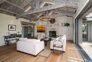 Rustic Living Room with Exposed beam, Chandelier, sliding glass door, Fireplace, stone fireplace, Paint 1, Built-in bookshelf