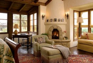 Mediterranean Master Bedroom with Exposed beam, stone fireplace, Wall sconce, Hardwood floors
