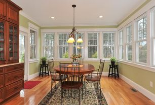 Contemporary Dining Room with Built-in bookshelf, Crown molding, Hardwood floors, Chandelier, French doors