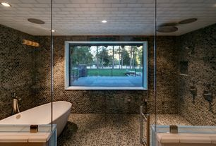 Contemporary Master Bathroom with Center drain freestanding soaking tub, Standing pebble wall tile, frameless showerdoor