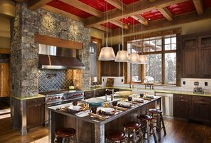 Rustic Kitchen with U-shaped, Corian counters, double oven range, Rustic log stools, Subway tile backsplash, Wall Hood, Flush