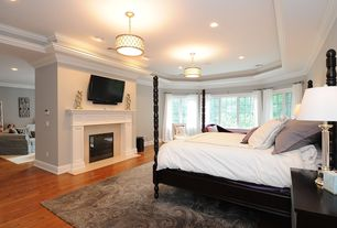 Traditional Master Bedroom with Crown molding, stone fireplace, Hardwood floors, Pendant light