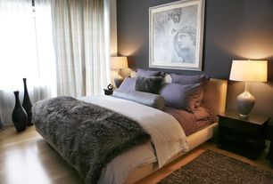 Contemporary Master Bedroom with Leather upholstered headboard, Ceramic bottle table lamp, Laminate floors