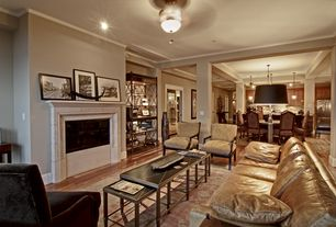 Traditional Living Room with flush light, stone fireplace, Hardwood floors, Crown molding, Columns