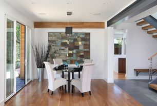 Contemporary Dining Room with Laminate floors, can lights, Standard height, sliding glass door, Pendant light