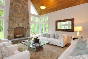 Cottage Living Room with White linen sofas and chairs, Hardwood floors, Casement, stone fireplace, Pendant light, Fireplace