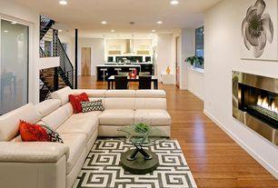 Modern Great Room with Laminate floors, Fireplace, Standard height, metal fireplace, Greek key area rug, flat door