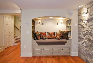 Traditional Living Room with Natural stone wall, Reading nook, Laminate floors, Built-in bookshelf, Hardwood floors