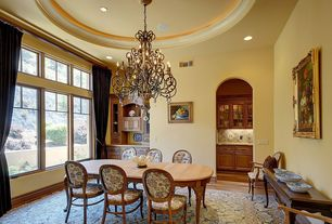 Traditional Dining Room with Casement, can lights, Chandelier, Hardwood floors, Built-in bookshelf, Standard height