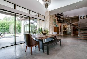 Modern Dining Room with Cathedral ceiling, Chandelier, Concrete floors, Transom window