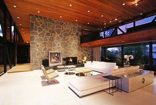 Modern Living Room with Loft, Concrete floors, Barcelona Chair - Tan, Rubik Round Coffee Table, flush light, stone fireplace