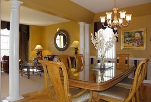 Traditional Dining Room with High ceiling, Chandelier, Wainscotting, Hardwood floors, Columns