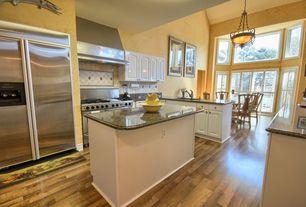 Mediterranean Kitchen with full backsplash, European Cabinets, Wall Hood, Limestone Tile, specialty door, double oven range