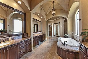 Traditional Master Bathroom with stone tile floors, drop in bathtub, Raised panel, Undermount sink, High ceiling, can lights
