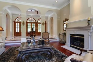 Traditional Living Room with High ceiling, Sunken living room, Hardwood floors, Cement fireplace, Crown molding, Columns