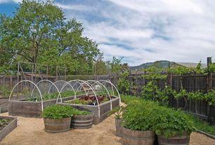 "Traditional Landscape/Yard with Birdseye Pea Gravel 1/8"" minus, Drip irrigation, Wood fence, Pathway, Garden, Raised beds"
