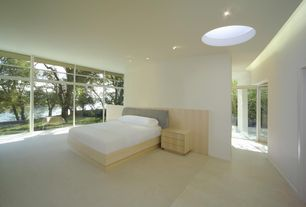 Modern Master Bedroom with can lights, Standard height, Skylight, Concrete floors, Built-in bookshelf, specialty window
