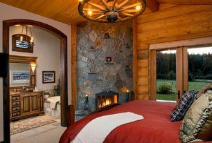 Country Master Bedroom with Stone fireplace surround, Sunset onyx stone 6 light faux candle chandelier, Exposed log wall