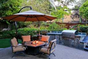 Traditional Patio with Brick patio edging, exterior tile floors, Fence, Fire pit coffee table, Cantilever outdoor umbrella